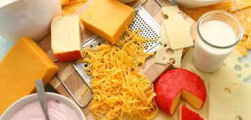 Group of dairy products including milk, yougurt, shredded cheese, powders, cheddar, swiss, dutch and jack cheese on a cutting board and cheese grater